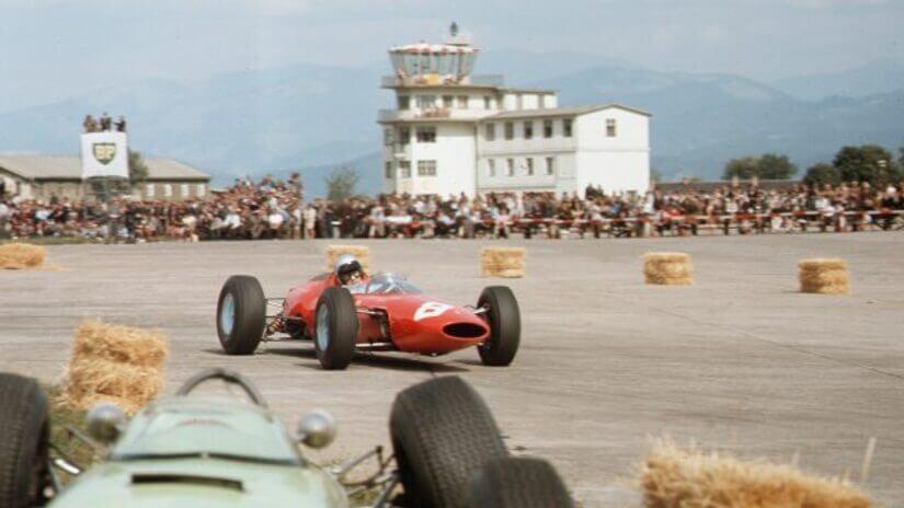 Lorenzo Bandini, ganador de la carrera, pasa junto a un coche roto.